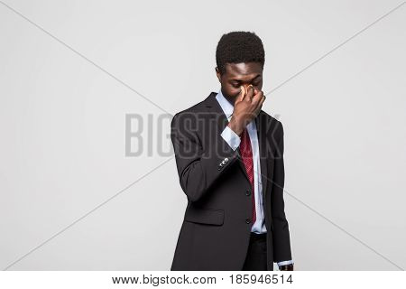 Frustrated Young African Man Massaging Nose And Keeping Eyes Closed While Standing Against Grey Back