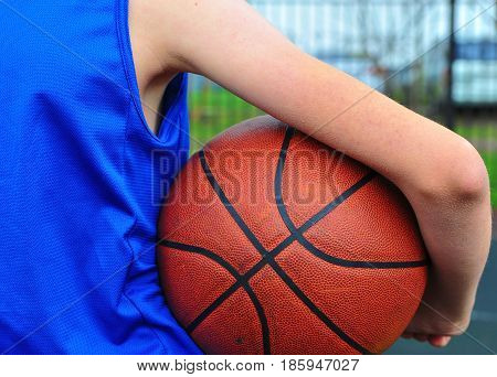 Child's hand holding the basketball ball outdoors