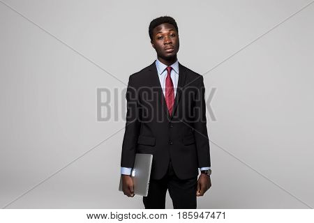 Handsome Young African Man In Formalwear Move With Laptop In Hands While Standing Against Grey Backg