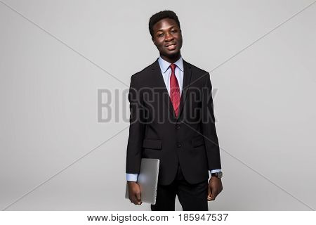 Handsome Young African Man Carrying Laptop And Looking At Camera While Standing Against Grey Backgro