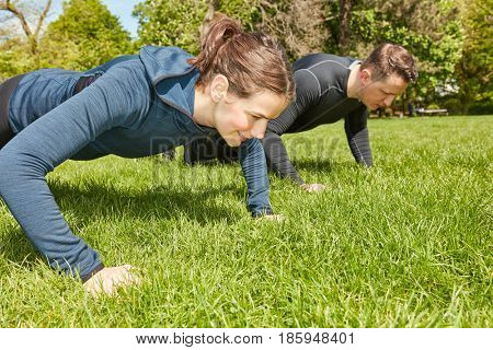Couple making push ups in the park as fitness training