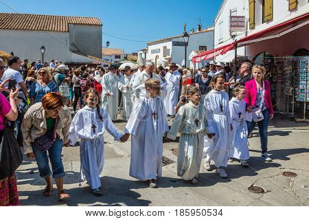 Saintes-maries-de-la-Mer, Provence, France - May 25, 2015. Religious feast in honor of the Holy Maries in Provence. Children in white robes and with crosses