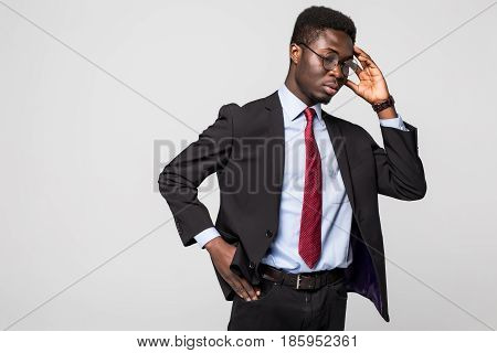 Handsome Young African Man Touching Head With Hand And Looking Uncertain While Standing Against Grey