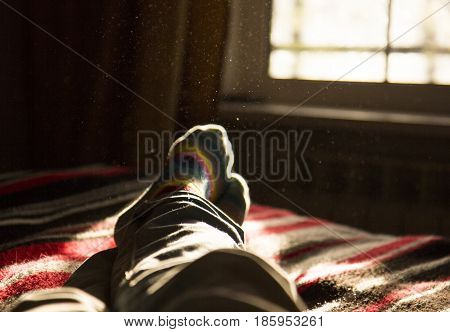lying and relaxing in bed opposite a window on a sunny day
