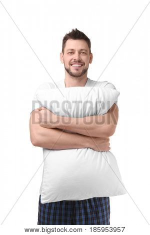 Young happy man in pajamas hugging orthopedic pillow on white background