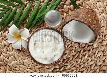 Fresh coconut oil in half of nut on wicker mat