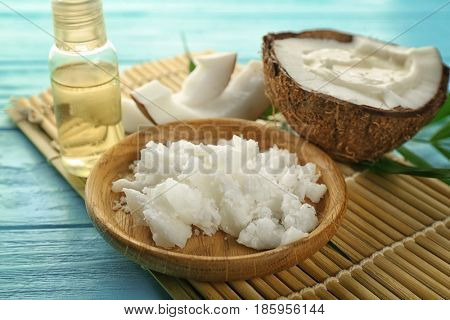 Plate with fresh coconut oil and half of nut on wooden table