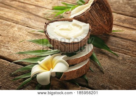 Fresh coconut oil in half of nut on wooden background