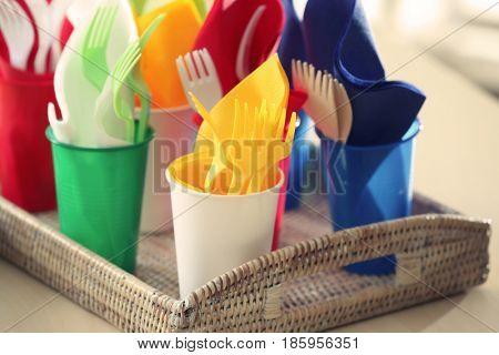 Plastic ware in wicker tray, closeup