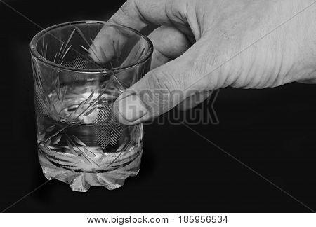 black-and-white image of male hands with a glass of water.