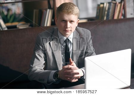 young businessman discussing business sitting at the table. looking right at you, folding his fingers together. next on the table is a laptop