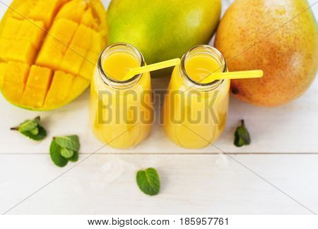 Fresh juice of a mango smoothies in a glass bottle and ripe mango fruit on a white wooden background.