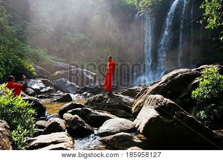 SIEM REAP, CAMBODIA - JANUARY 27, 2015: Unidentified novice monks taking picture in Phnom Kulen waterfall in Kulen National Park, Siem Reap Province, Cambodia.