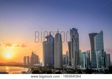 The skyscrapers in the skyline of the commercial center of Doha the capital of the Arabian Gulf country Qatar at sunset.