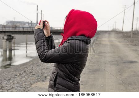 A chinese woman wearing a red hoodie taking pictures with a smart phone near a chinese ethanol production factory along a dirt road in the city of Zhaodong China in Heilongjiang province on an overcast day.