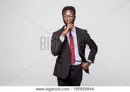 Closeup Portrait Young Serious African Businessman Placing Finger On Lips Saying, Shhh, Be Quiet, Si