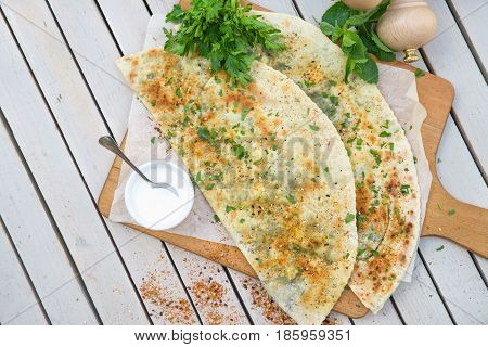 Typical Turkish meal Gozleme with herb and cheese on light wooden cutting board on table.