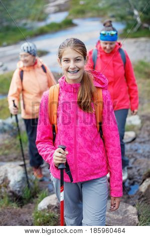 Happy hiking girl with trekking sticks in the mountains with her family. Norway