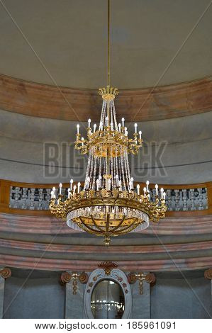 Crystal and golden chandelier in a fancy palace ballroom