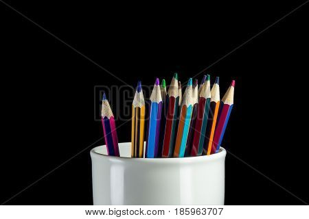 Sharp tips of colored pencils sharpen, on a dark wooden background