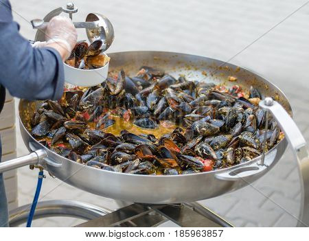 The Chef Puts Mussels. Lovely Lunch Or Dinner. Live Healthy Food. Close-up Of A Diver In His Hand An