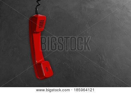 Handset From Landline Red Phone On A Gray Wall Background