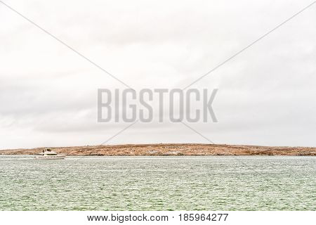 LANGEBAAN SOUTH AFRICA - MARCH 31 2017: A catamaran on the Langebaan lagoon with thousands of cormorants on Schaapen Island in the back