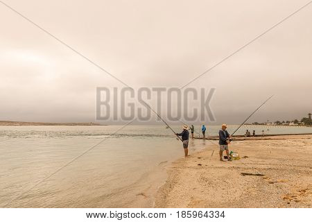 LANGEBAAN SOUTH AFRICA - MARCH 31 2017: Unidentified anglers at sunset at the Langebaan Lagoon on the Atlantic Coast of the Western Cape Province