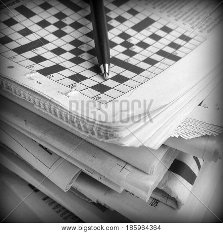 Pen and Crossword Puzzle on top of a stack of newspapers with a shallow depth of field. A vignette has been added for effect