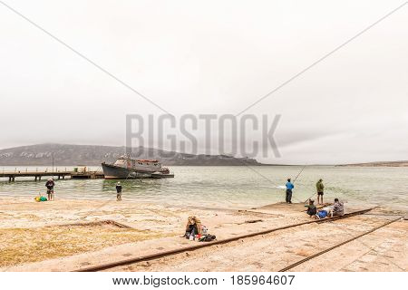 LANGEBAAN SOUTH AFRICA - MARCH 31 2017: A boat anchored at a pier and anglers at a boat launching site at Langebaan on the Atlantic Coast of the Western Cape Province