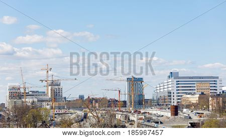 STOCKHOLM SWEDEN - MAY 01 2017: Cranes building houses in the new district New Hagastaden and the hospital Nya Karolinska in Stockholm. May 01 2017 in Stockholm Sweden