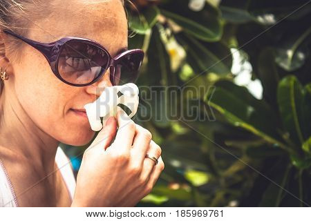 Woman smelling flower hanging it in hands