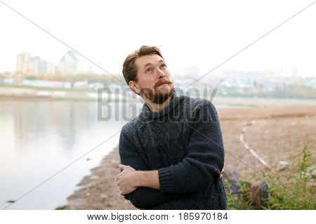 Handsome bearded man on the background of the river.