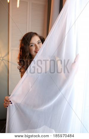 Beautiful young woman hiding behind the curtain.