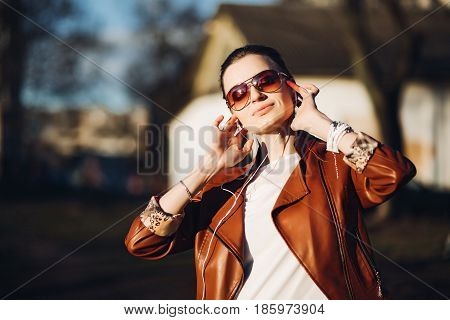Portrait of smiling relaxed woman in sunglasses, walking at street in sunny weather, listening music. Beautiful brunette girl in leather jacket holding headphones, enjoying with closed eyes.