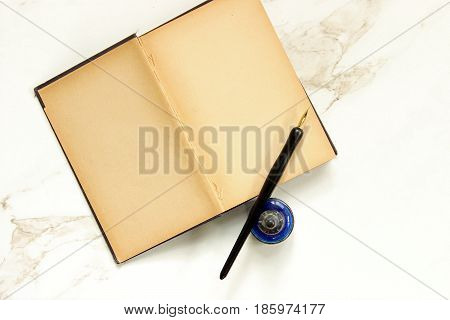 Vintage book open to blank pages with pen and ink. White marble copy space.