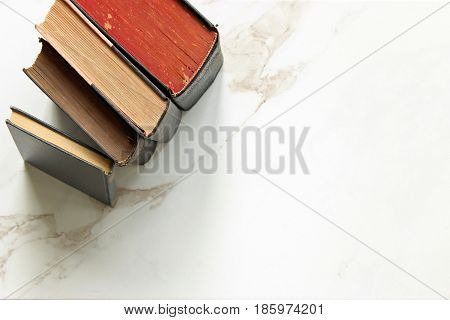 Vintage books stacked framing white open marble copy space.