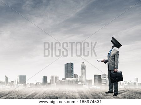 Faceless businessman with camera zoom instead of head against cityscape background