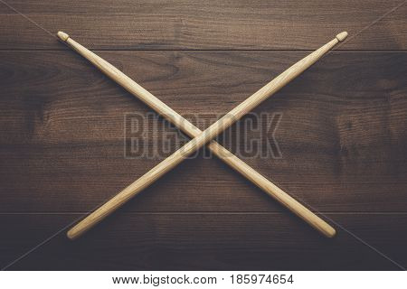 pair of wooden drumsticks crossed on wooden table