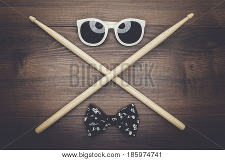 pair of wooden drumsticks crossed on wooden table, sunglasses and bow tie