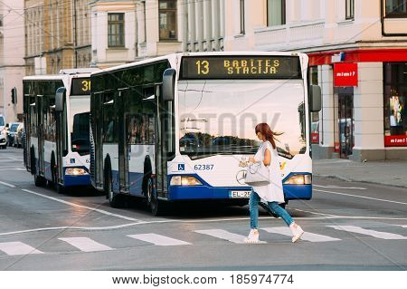 Riga, Latvia - July 2, 2016: Woman crossing road at a pedestrian crossing before staying public trolleybus.