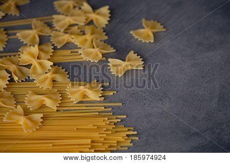 Composition of uncooked italian pasta. Spaghetti farfalle fusilli on dark wooden background. Raw pasta background.