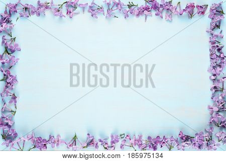 Frame of lilac flowers on blue wooden background