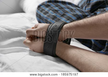 Male hands tied up with belts in bed