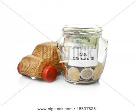 Glass jar with money and wooden car toy on white background