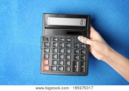 Female hand holding calculator on color background