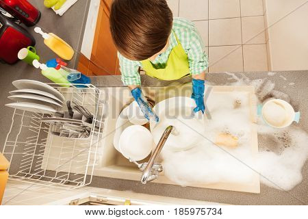 Top view portrait of of kid boy rinsing dishes under running water in the sink full of soap suds