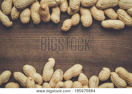 many roasted peanuts on the wooden table background with copy space
