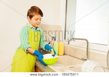 Kid boy washing dishes under running water standing in the kitchen against the wall with copy-space