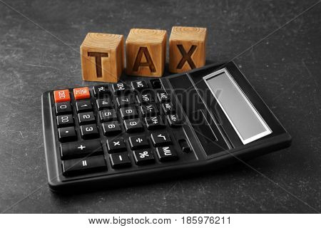 Wooden blocks with word TAX and calculator on gray background
